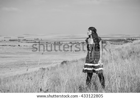 Black and white portrait of beautiful brunette bohemian woman standing on a hill in a field of grass. - stock photo