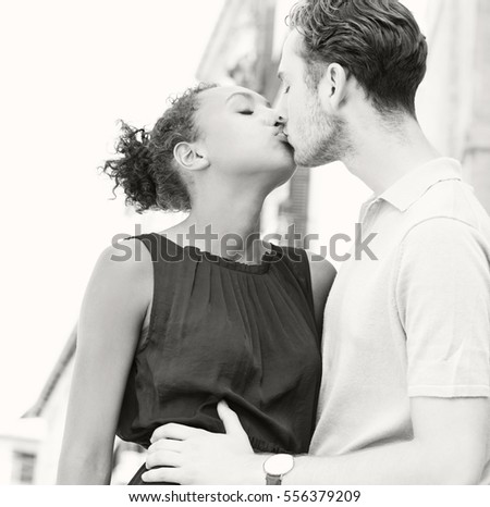 Black and white portrait of beautiful ethnically diverse couple hugging and kissing in a destination city, romantic outdoors. Boyfriend and girlfriend together on holiday, travel recreation lifestyle.
