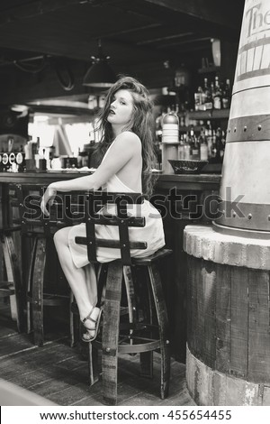 Black and white portrait of beautiful girl in elegant dress, pub bar background
