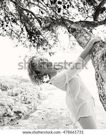 Black and white portrait of beautiful healthy mature woman relaxing in nature destination, playful around tree trunk enjoying a holiday, nature outdoors. Healthy lifestyle, mature woman, exterior.