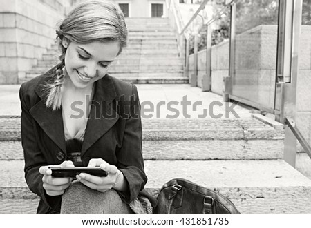 Black and white portrait of beautiful professional young woman sitting on city stairs using a smart phone to work, outdoors. Business woman using technology in classic exterior, networking lifestyle. - stock photo