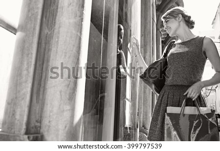 Black and white portrait of beautiful young tourist woman with shopping bags looking at city fashion store window, smiling outdoors. Consumer recreation girl, exclusive expensive lifestyle exterior. - stock photo