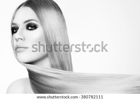 Black and white portrait of beautiful young woman with smokey eyes and long straight hair