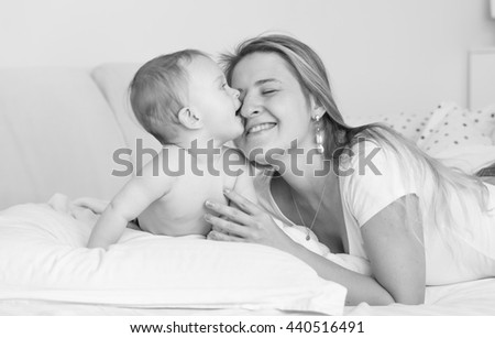Black and white portrait of cheerful mother hugging and kissing her baby boy on bed - stock photo