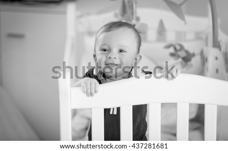Black and white portrait of cute baby boy standing at his crib - stock photo