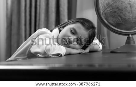 Black and white portrait of cute girl fell asleep while doing homework - stock photo