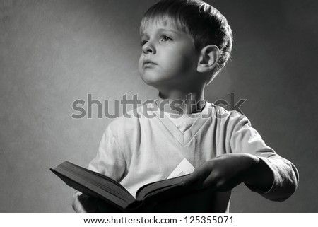 black and white portrait of cute little boy with book looking up - stock photo