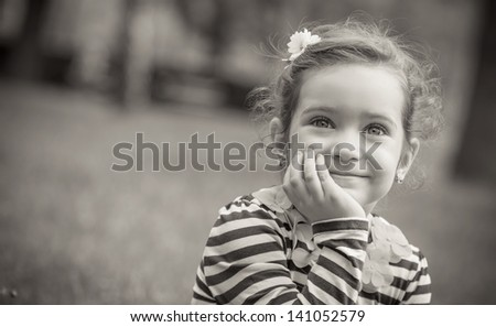 Black and white portrait of cute little girl in a park. Close-up of beautiful child, outdoors - greyscale - stock photo