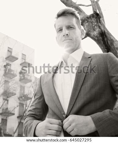 Black and white portrait of elegant business man grooming against flare sky in financial city district, confident, looking to camera outdoors. Powerful suit professional male, aspirational lifestyle.