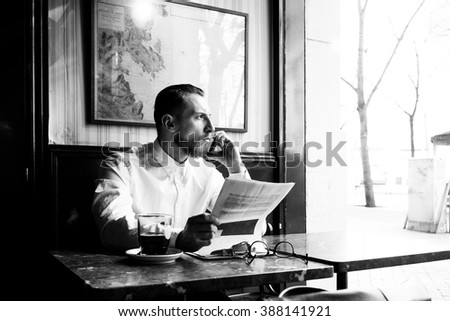 Black and white portrait of elegant business man looking over some paperwork and talking on the smart-phone while sitting next to big window in coffee shop