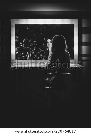 Black and white portrait of elegant woman posing in dressing room at mirror - stock photo