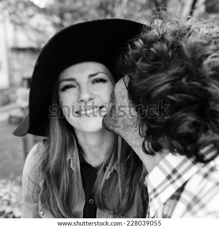 Black and white portrait of emotional young Italian couple in the park - stock photo