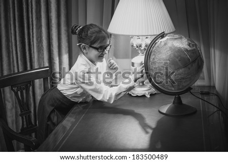 Black and white portrait of girl studying earth globe - stock photo