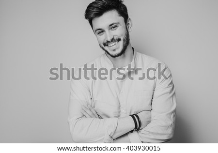 black and white portrait of handsome smiling man isolated on gray studio background posing to the camera - stock photo
