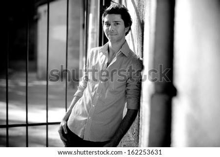Black and white portrait of handsome trendy man leaning against wall on street - stock photo