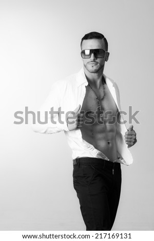 black and white portrait of handsome young male model posing holding his unbuttoned shirt - stock photo