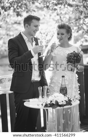 Black and white portrait of happy bride and groom drinking champagne at outdoor wedding ceremony - stock photo