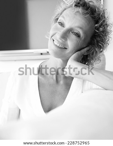 Black and white portrait of healthy and successful mature professional woman sitting on a sofa at home relaxing indoors, smiling with a flat tv screen in the background. Aspirational beauty lifestyle. - stock photo