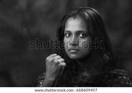 Black and white portrait of indian woman shows her fist
