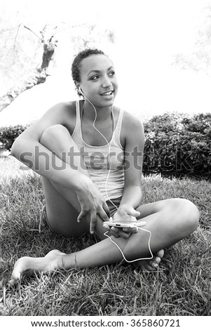 Black and white portrait of joyful african american teenager girl smiling using smartphone to listen to music, sitting on grass in park, outdoors. Adolescent technology lifestyle, exterior holiday. - stock photo