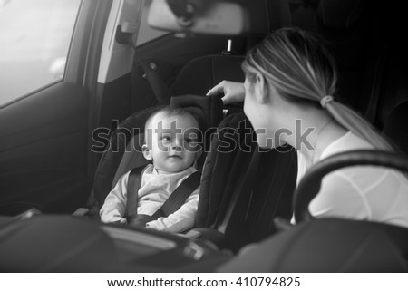 Black and white portrait of mother looking at baby sitting on car front seat - stock photo