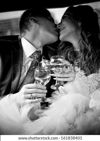 Black and white portrait of newly married couple kissing in car while holding glasses of champagne - stock photo