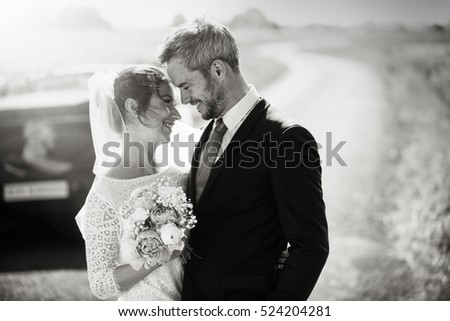 Black and white. portrait of newlyweds entwined , holding a bouquet, on a country road. their car is behind them, waiting to drive them on  honeymoon.