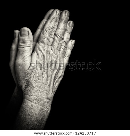 Black and white portrait of old wrinkled hands praying isolated on black with space for text - stock photo