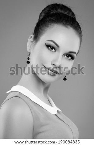 Black and white portrait of retro stylish woman with professional makeup and hairdo. Young pretty smiling Caucasian female model posing in studio.  - stock photo