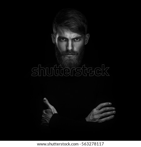 Black and white portrait of serious young man with folded and crossing hands standing isolated on