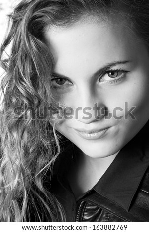 Black and white portrait of sexy woman with curly hair smiling snidely