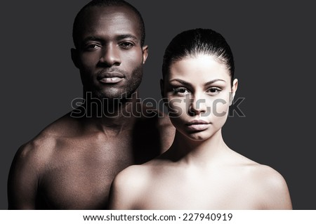 Black and white. Portrait of shirtless African man and Caucasian woman bonding to each other and looking at camera while standing against grey background  - stock photo