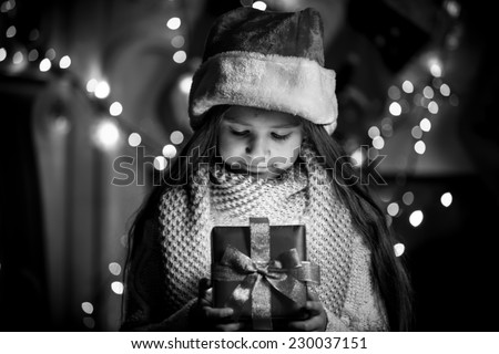 Black and white portrait of smiling girl opening Christmas present box - stock photo