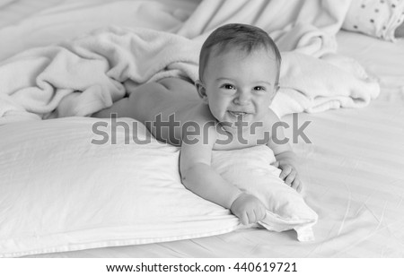 Black and white portrait of smiling naked baby lying on pillows on big bed - stock photo