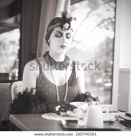 Black and White Portrait of The Beautiful Retro Woman Pouring Tea from a Teapot in the Cafe in Black Lace and Accessories in Style 1920s - 1930s  - stock photo