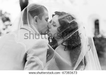 black and white portrait of the bride and groom kissing behind veil
