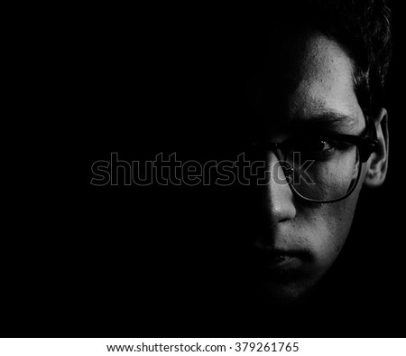 black and white portrait of the face of the young man in glasses in low key