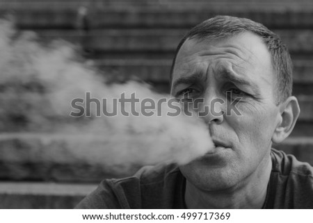 Black and white portrait of the man who exhales the smoke