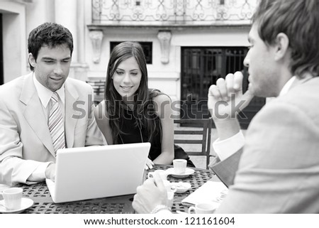 Black and white portrait of three business people sharing a table at a coffee shop terrace, having a meeting and talking while using technology in the financial city district.
