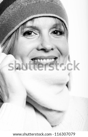 black and white portrait of warm dressed middle aged woman over a white background - stock photo