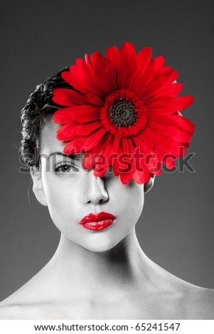 black and white portrait of woman with red lips and red flower on her face.