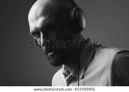 Black and white portrait of young bald man with earphones