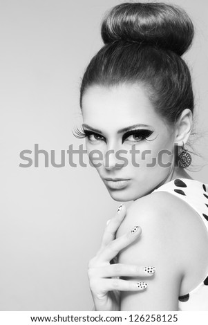 Black and white portrait of young beautiful girl with fancy cat eyes and big retro hair bun - stock photo