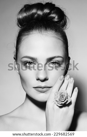 Black and white portrait of young beautiful girl with trendy hair bun - stock photo