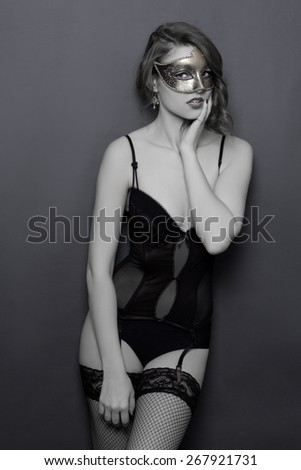 black and white portrait of young beautiful sexy woman in lingerie and mask - stock photo