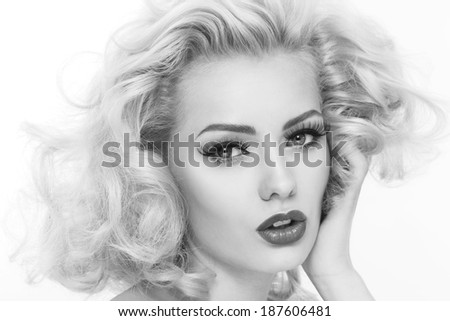 Black and white portrait of young beautiful woman with blond curly hair and false eyelashes - stock photo