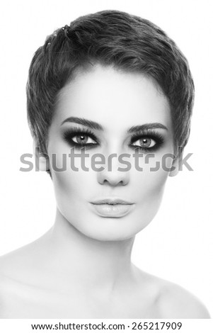 Black and white portrait of young beautiful woman with stylish short haircut and smoky eyes over white background - stock photo