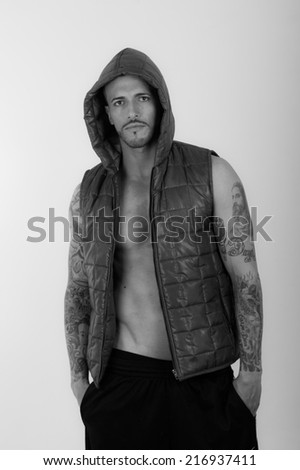 Black and white portrait of Young brunette shirtless male model wearing a vest - stock photo