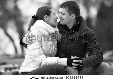 Black and white portrait of young couple hugging and looking at each other - stock photo