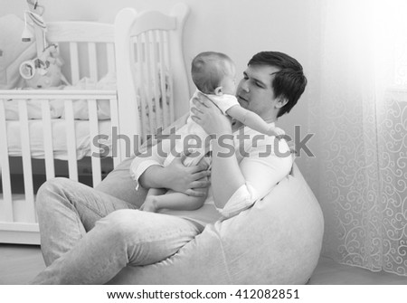 Black and white portrait of young father holding his 6 months baby son - stock photo
